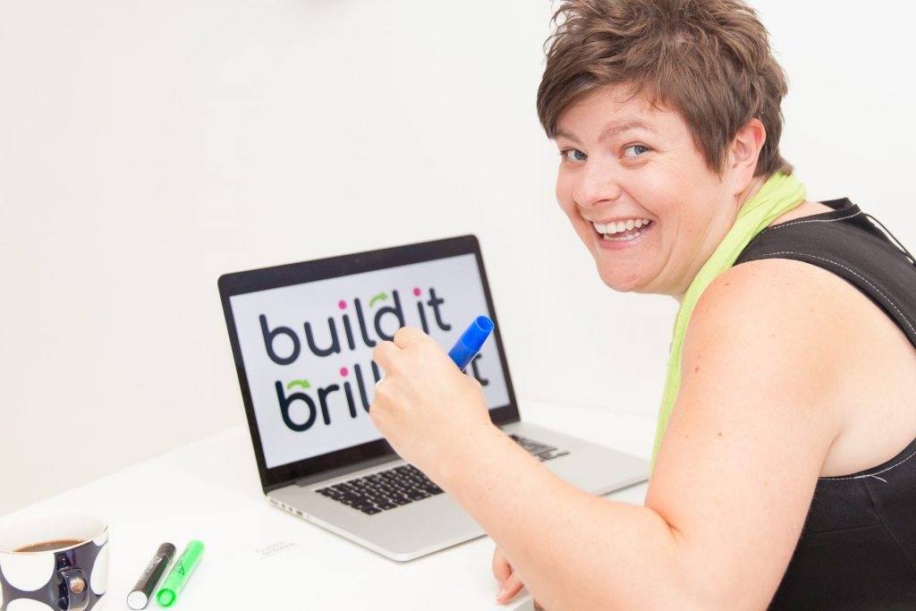 Zoe, founder of Build It Brilliant cheeky face with laptop